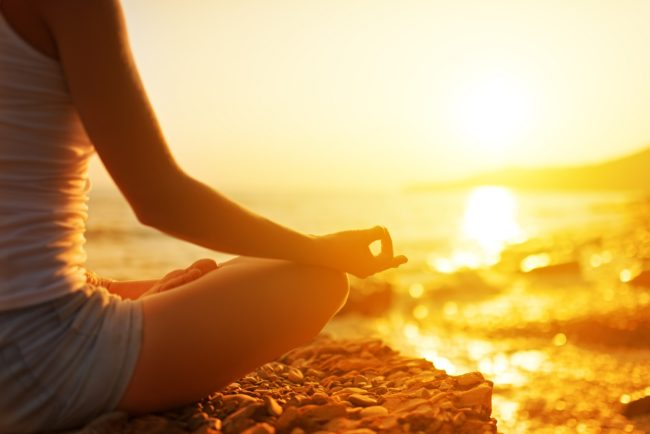 hand of a woman meditating in a yoga pose on the beach